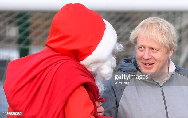British Prime Minister Boris Johnson jokes with a man dressed as Father Christmas during the warm up before a girls' soccer match between Hazel Grove...