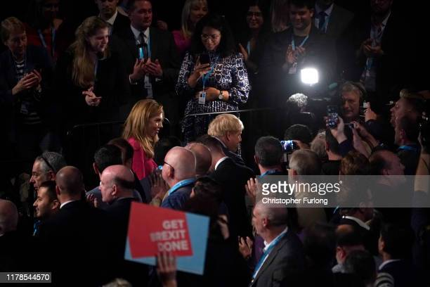 British Prime Minister Boris Johnson leaves the auditorium with girlfriend Carrie Symonds after delivering his keynote speech onstage on the final...