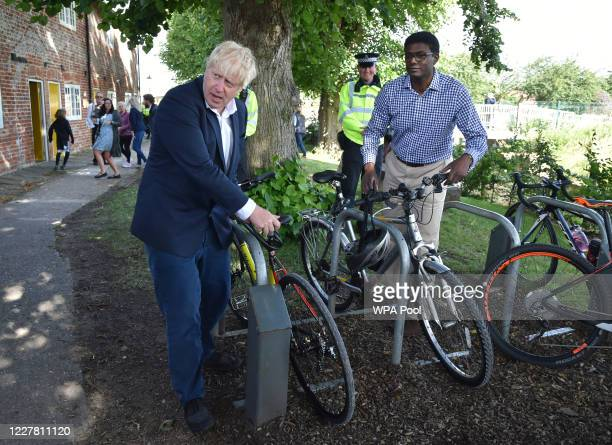 British Prime Minister Boris Johnson locks up his bicycle at the Canal Side Heritage Centre in Beeston on July 28 2020 in Beeston near Nottingham...