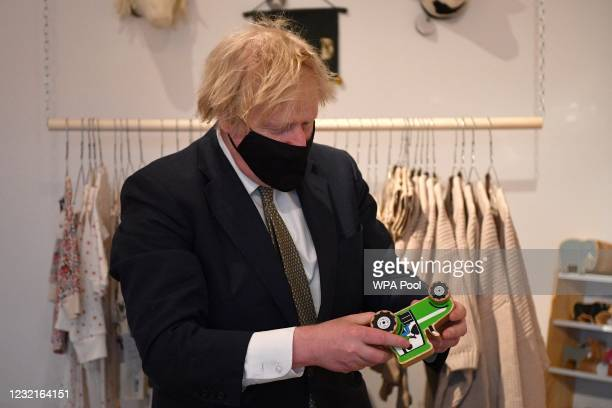 British Prime Minister Boris Johnson looks at a toy tractor in a shop before purchasing it during a visit to Lemon Street Market on April 7, 2021 in...