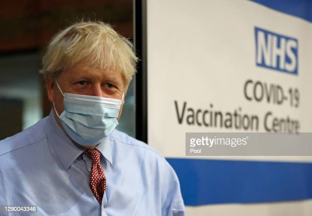British Prime, Minister Boris Johnson looks on after nurse Rebecca Cathersides administered the Pfizer-BioNTech COVID-19 vaccine to Lyn Wheeler at...