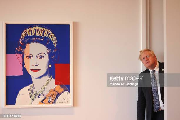 British Prime Minister Boris Johnson looks up at a ceiling ornament as he awaits the start of his meeting with Amazon founder Jeff Bezos at the UK...