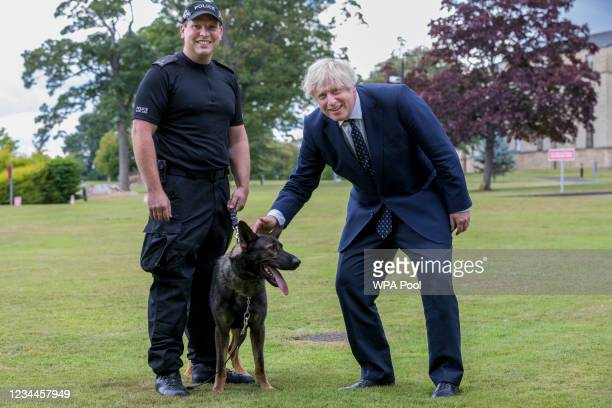 British Prime Minister Boris Johnson meets dog handler PC Chris Morrison with dog Eli during a visit to the Scottish Police College at Tulliallan on...