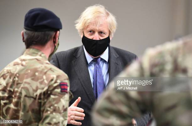 British Prime Minister Boris Johnson meets troops as they set up a vaccination centre in the Castlemilk district on January 28, 2021 in Glasgow,...