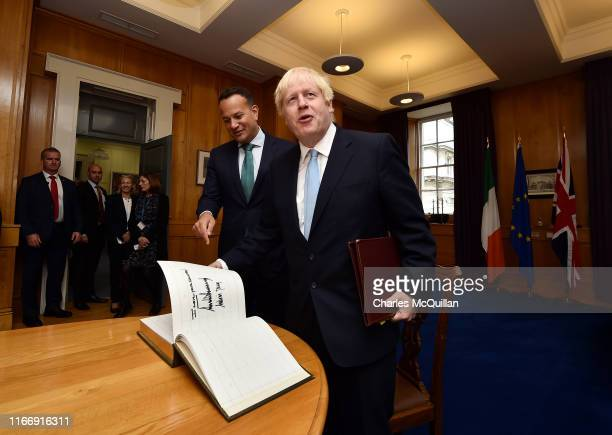British Prime Minister Boris Johnson opens a guestbook at the page signed by U.S President Donald Trump and U.S First Lady Melania Trump during his...