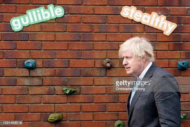 """British Prime Minister Boris Johnson passes the words """"gullible"""" and """"stealthy"""" during a visit to St Mary's CE Primary School on March 1, 2021 in..."""