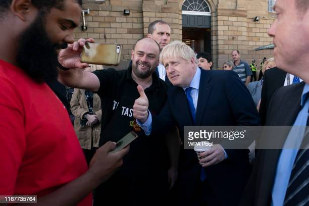 British Prime Minister Boris Johnson poses for a selfie with a member of the public during a visit to Doncaster Market on September 13 2019 in...