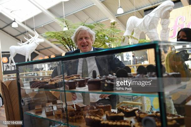 British Prime Minister Boris Johnson reacts as he looks at a display of cakes and desserts as he talks with business owners inside Lemon Street...