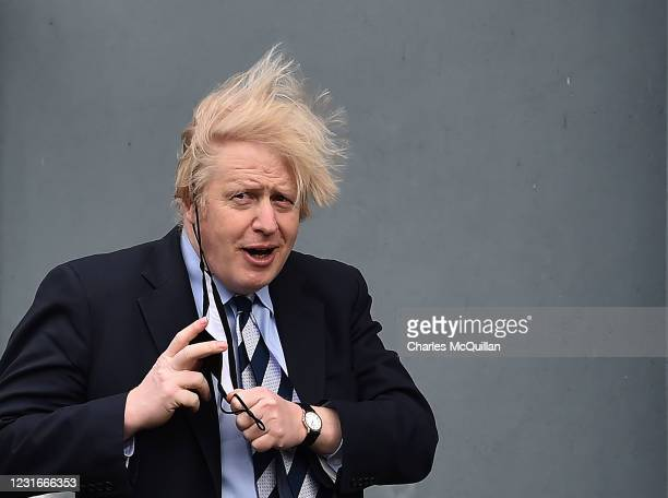 British Prime Minister Boris Johnson removes his face mask as he leaves the Lakeland Forum vaccination centre on March 12, 2021 in Enniskillen,...