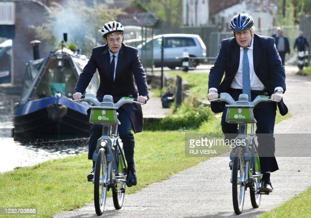 British Prime Minister Boris Johnson rides a bike near the towpath of the Stourbridge canal with mayor for West Midlands Andy Street during a...