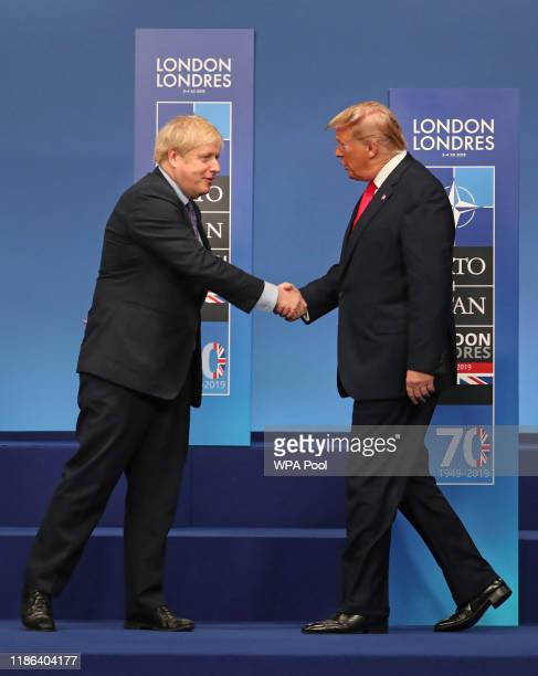 British Prime Minister Boris Johnson shakes hands with US President Donald Trump onstage during the annual NATO heads of government summit on...