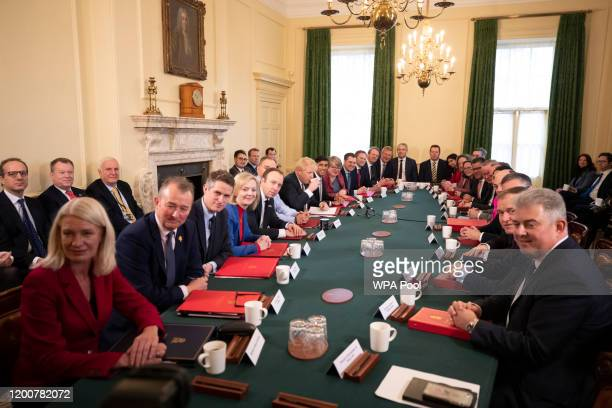 British Prime Minister Boris Johnson sips a drink at the beginning of his first Cabinet meeting after a reshuffle the day before, inside 10 Downing...