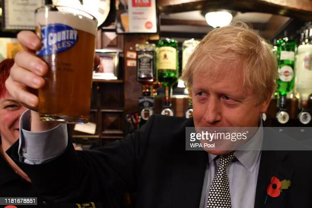 British Prime Minister Boris Johnson sips a pint of beer as he campaigns ahead of the general election at the Lynch Gate Tavern on November 11 2019...