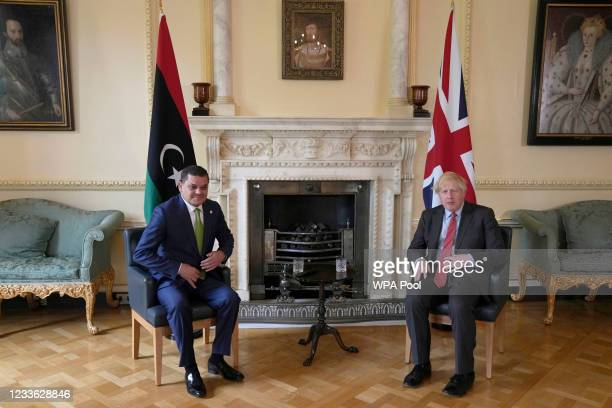 British Prime Minister Boris Johnson sits with Libya's interim prime minister Abdul Hamid Dbeibah ahead of a meeting at Downing Street on June 24,...