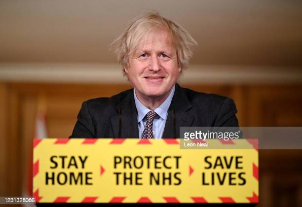 British Prime Minister Boris Johnson smiles during a televised press conference at 10 Downing Street on February 22, 2021 in London, England. The...