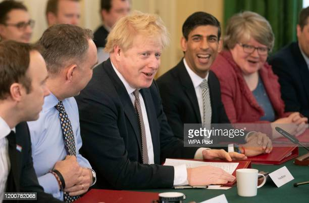 British Prime Minister Boris Johnson speaks during his first Cabinet meeting flanked by his new Chancellor of the Exchequer Rishi Sunak, fourth left,...
