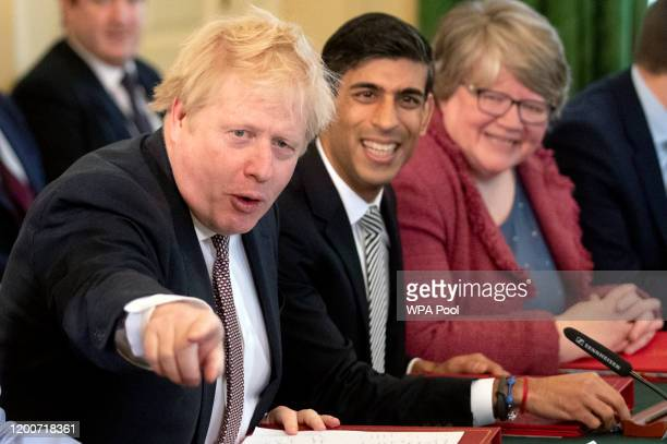 British Prime Minister Boris Johnson speaks flanked by his new Chancellor of the Exchequer Rishi Sunak following a reshuffle at Downing Street on...