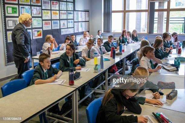 British Prime Minister Boris Johnson speaks to year 7 pupils on their first day back at school during a visit to Castle Rock school on August 26,...