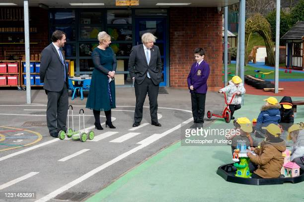 British Prime Minister Boris Johnson speaks with Head Boy Jonah Bradbury and Headteacher Clare Morton in the playground during a visit to St Mary's...