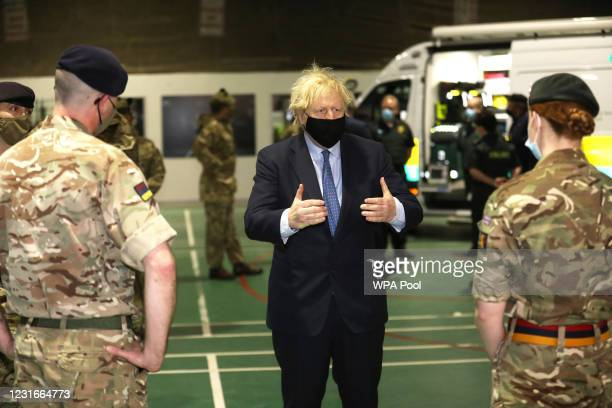 British Prime Minister Boris Johnson speaks with Military medics during a visit to Joint Helicopter Command Flying Station Aldergrove on March 12,...