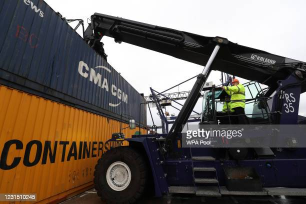 British Prime Minister Boris Johnson stands on a vehicle to move shipping containers on March 4, 2021 in Teesport, England. Teesport has been chosen...
