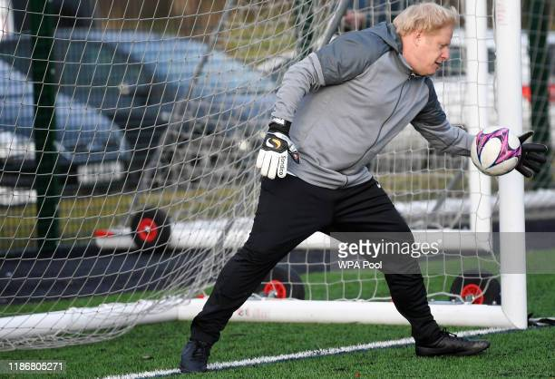 British Prime Minister Boris Johnson takes a turn in goal during the warm up before a girls' soccer match between Hazel Grove United JFC and Poynton...