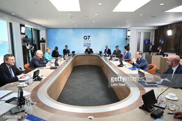 British Prime Minister Boris Johnson takes part in a meeting next to US President Joe Biden and French President Emmanuel Macron, Canadian Prime...