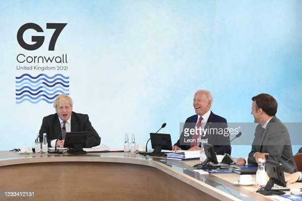 British Prime Minister Boris Johnson talks next to US President Joe Biden and French President Emmanuel Macron at the G7 summit in Carbis Bay on June...
