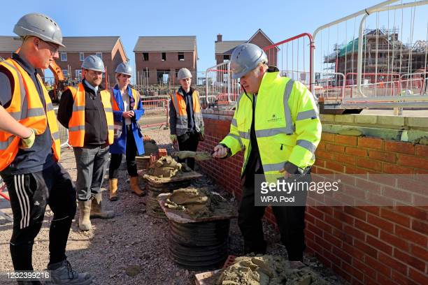 British Prime Minister Boris Johnson tries his hand at bricklaying during a visit to a Barratt Homes development on April 19, 2021 in Oldbury, United...