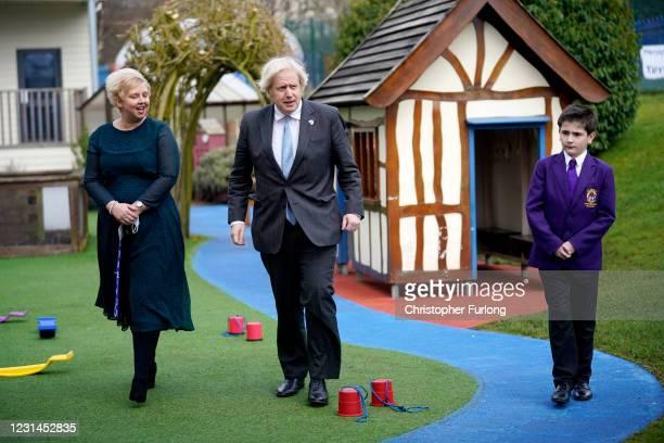 British Prime Minister Boris Johnson walks through the playground with Headteacher Clare Morton and Head Boy Jonah Bradbury during a visit to St...