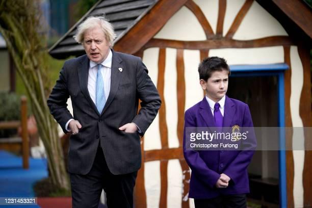 British Prime Minister Boris Johnson walks through the playground with and Head Boy Jonah Bradbury during a visit to St Mary's CE Primary School on...