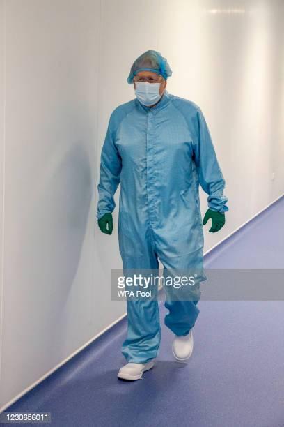 British Prime Minister Boris Johnson walks towards a viewing window where technicians are manufacturing the Astra Zeneca Covid-19 vaccine as he...