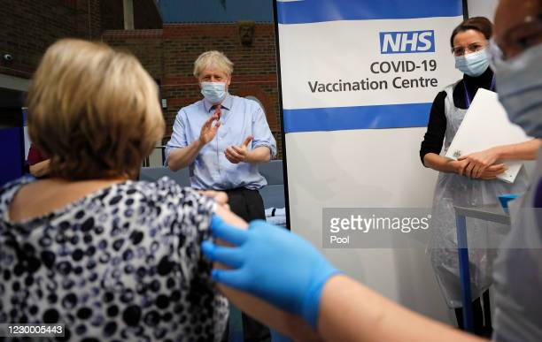 British Prime Minister, Boris Johnson watches as nurse Rebecca Cathersides administers the Pfizer-BioNTech COVID-19 vaccine to Lyn Wheeler at Guy's...