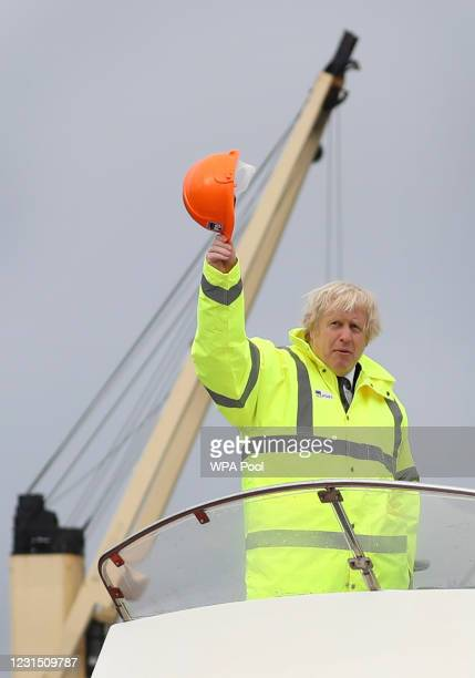 British Prime Minister Boris Johnson waves his hard hat as he travels on board a boat on the River Tees on March 4, 2021 in Teesport, England....