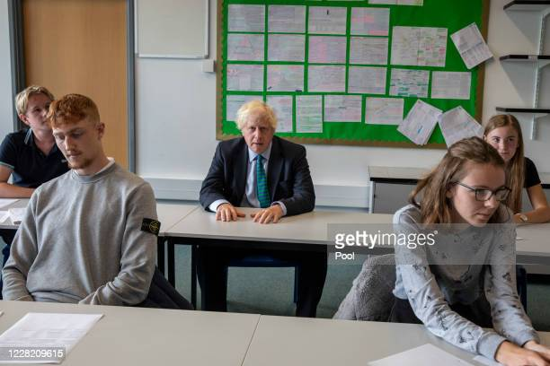 British Prime Minister Boris Johnson, wearing the school tie he was presented with on arrival, sits with year 11 pupils on their first day back at...