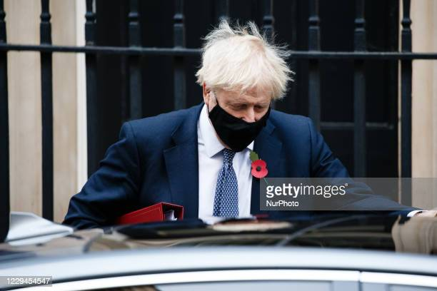 British Prime Minister Boris Johnson wears a face mask and remembrance poppy as he leaves 10 Downing Street heading for his weekly Prime Minister's...