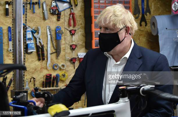 British Prime Minister Boris Johnson wears a face mask as he talks to the owner of the the Cycle Lounge Rodney Rouse in a bicycle repair shop Beeston...