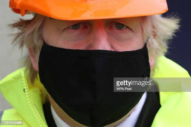 British Prime Minister Boris Johnson wears a hard hat and mask during a visit to Teesport on March 4, 2021 in Teesport, England. Teesport has been...