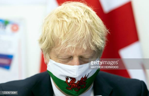 British Prime Minister Boris Johnson wears a Welsh flag face mask holds an ice cream as he visits Marcos cafe in Barry Island during the Senedd...