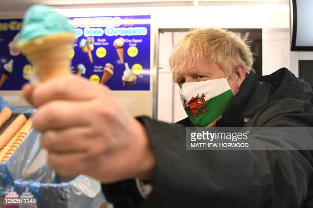 British Prime Minister Boris Johnson wears a Welsh flag face mask and gives a thumbs up as he visits Marcos cafe in Barry Island during the Senedd...