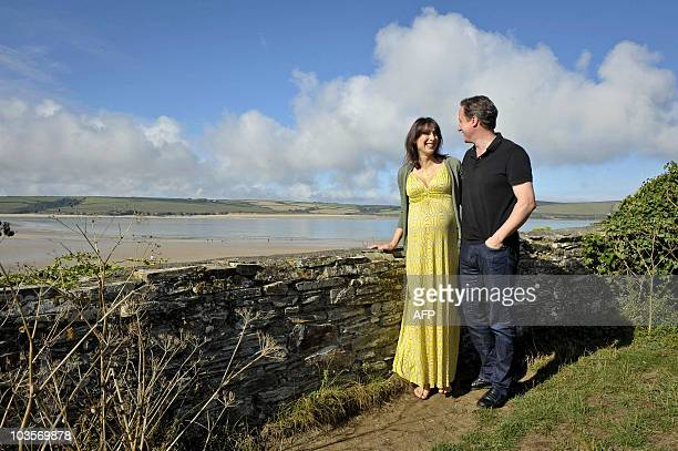 British Prime Minister David Cameron accompanied by his wife Samantha pose on August 22 2010 on the coastal path at Daymer Bay beach in Cornwall...