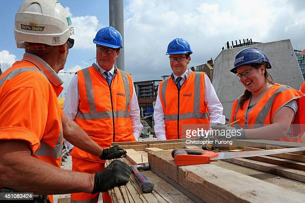British Prime Minister David Cameron and British Chancellor George Osborne chat to workers as they tour building works at Manchester's Victoria...