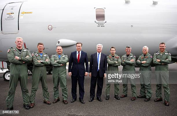 British Prime Minister David Cameron and Defence Secretary Michael Fallon pose for a photograph with the British crew of a Boeing P8 Poseidon...