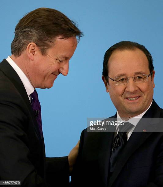 British Prime Minister David Cameron and French President Francois Hollande shake hands as they take part in a press conference during the joint...
