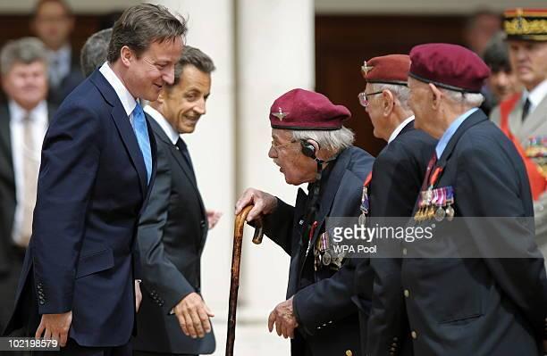British Prime Minister David Cameron and French President Nicolas Sarkozy talk with Legion de Honeur recipients and World War II veterans Walter...