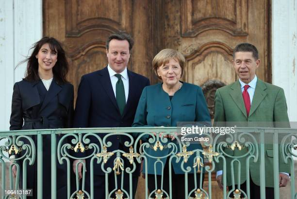 British Prime Minister David Cameron and German Chancellor Angela Merkel look out with their spouses Samantha Cameron and Joachim Sauer following the...