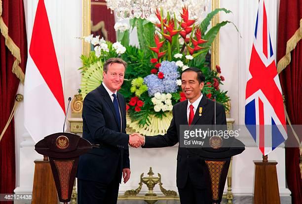 British Prime Minister David Cameron and Indonesian President Joko Widodo shake hands after the signing of several memorandums of understanding...
