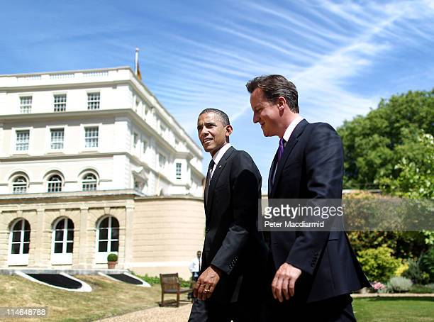 British Prime Minister David Cameron and US President Barack Obama walk in the gardens of Lancaster House after holding a joint press conference on...