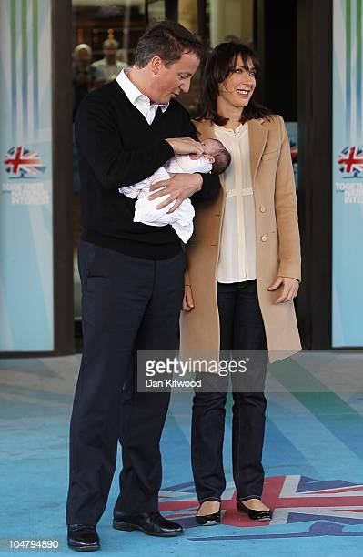 British Prime Minister David Cameron and wife Samantha pose for photographs with their baby daughter Florence Rose Endellion at the Conservative...