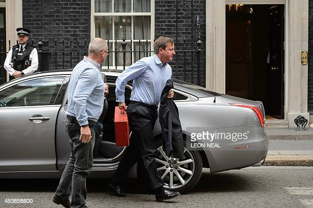 British Prime Minister David Cameron arrives back in Downing Street central London on August 20 2014 David Cameron broke off his holiday Wednesday...